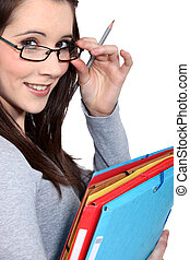 portrait of female student with glasses lowered holding files