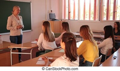 female teacher lecturing to students at auditorium - ...