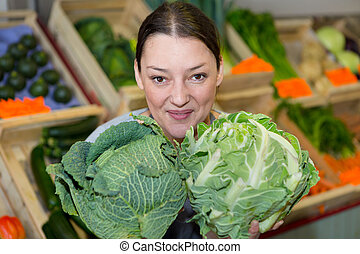 portrait of female vendor holding cabbage