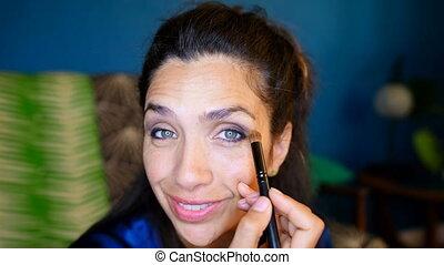 Female video blogger applying eyeshdow at home 4k - Portrait...