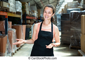 Portrait of female worker in apron with arms crossed standing in warehouse
