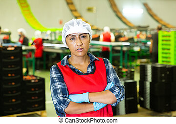 Portrait of female worker in uniform with arms crossed standing in warehouse