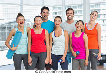 Portrait of fit people smiling in exercise room - Portrait...