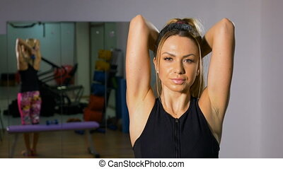 Portrait of fit woman exercising with light weight dumbbells in her hands at the gym