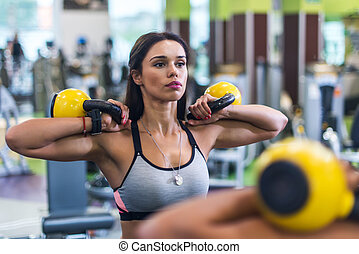 Portrait of fit woman looking at mirror, exercising with kettlebell in gym