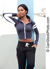 fit young african american woman leaning against pole outside