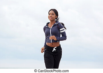 fit young african american woman running outdoors