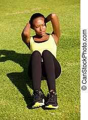 fit young african woman doing stomach crunch