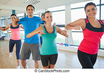 Portrait of fitness class and instructor doing pilates exercise