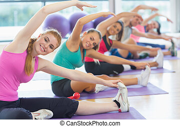 Portrait of fitness class and instructor doing stretching...