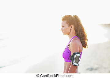 Portrait of fitness young woman in headphones on beach looking on copy space