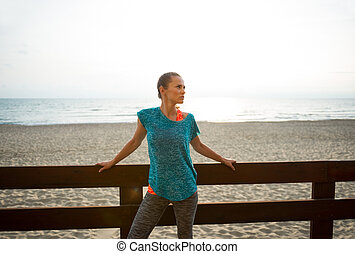 Portrait of fitness young woman on beach in the evening