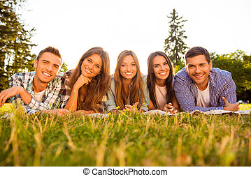 Portrait of five cheerful smiling friends lying on grass