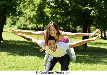 Portrait of flying happy beautiful couple outdoors with spread hands