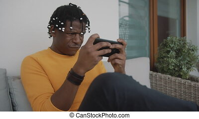 Portrait of focused african american black man playing games on the smartphone . High quality 4k footage