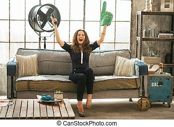 Portrait of football fan woman watching tv in loft apartment...