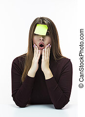 Portrait of Forgetful Surprised Caucasian Woman in Burgundy Turtleneck Sweater With Yellow Sticky Note on Her Forehead. Posing Against White Background.