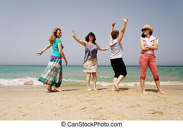Portrait of four 40 years old women walking on seaside