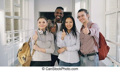 Portrait of four positive multi-ethnic male and female...