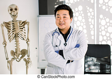 Portrait of friendly Asian Korean doctor man at his office smiling to camera. Young smiling clinician in white coat crossing arms on chest, human skeleton on the background