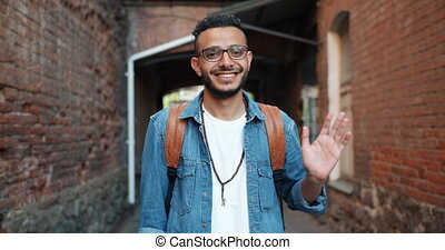 Portrait of friendly cheerful Arabian man waving hand...