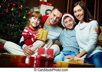 Christmas eve - Portrait of friendly family looking at ...