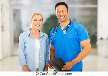 medical doctor standing with senior patient