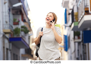 friendly young woman walking in the city and talking on mobile phone