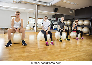 Portrait Of Friends Sitting On Exercise Ball At Gym
