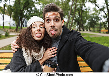 Portrait of funny couple man and woman 20s taking selfie photo, while sitting on bench in green park