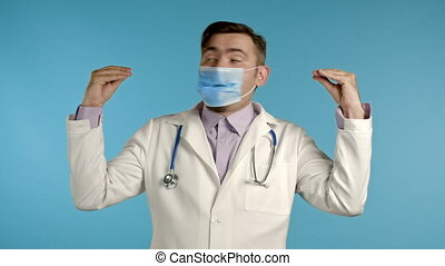 Portrait of funny doctor in medical coat showing bla-bla-bla gesture with hands and mouth isolated on blue background. Empty promises, blah concept. Lier