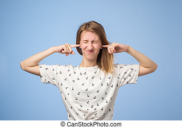 Portrait of funny european woman plugging ears, closing her eyes, pretending not to hear wat she is told
