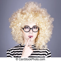 Portrait of funny girl in blonde wig. Studio shot.