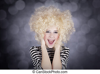 Portrait of funny girl in blonde wig. Studio shot.