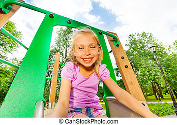 Portrait of funny girl on playground chute