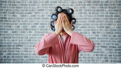 Portrait of funny girl with hair curlers playing hide and...