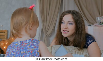Portrait of funny little girl and her mother at home