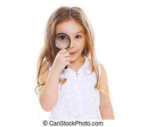 Portrait of funny little girl looking through a magnifying glass having fun