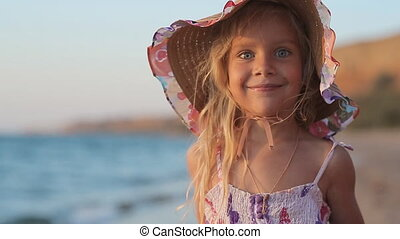 Portrait of funny little girl on the sea
