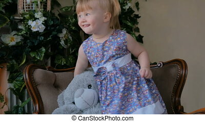 Portrait of funny little girl with bear doll at home