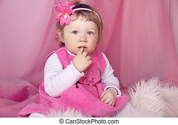 Portrait of funny lovely little girl, finger in mouth