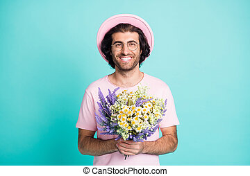 Portrait of funny nice guy hold flowers wear pink cap t-shirt spectacles isolated on teal color background