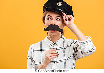 Portrait of funny woman in plaid shirt and police cap holding paper moustache at her face, isolated over yellow background