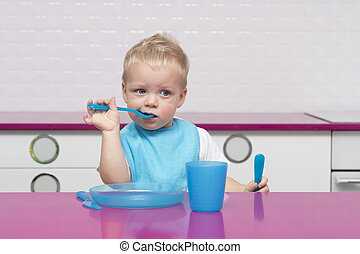 Portrait Of funny Young Baby Boy in a blue bib with fork and knife in his hands In High Chair in the modern kitchen eating something