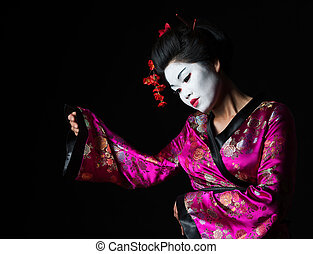 Portrait of geisha presenting something isolated on black