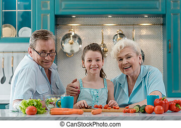 Portrait of girl and grandparents at the table in kitchen