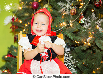 Portrait of girl child in suit a red hat for Christmas around a fir-tree decorated. Kid on holiday new year