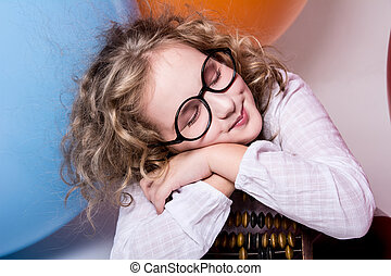 Portrait of girl dreaming smiling in glasses with eyes closed against the background of large rubber balls. Beautiful little girl sleeping on a wooden abacus