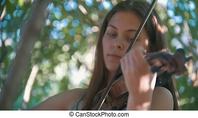 Portrait of girl hipster playing a violin in the park at...