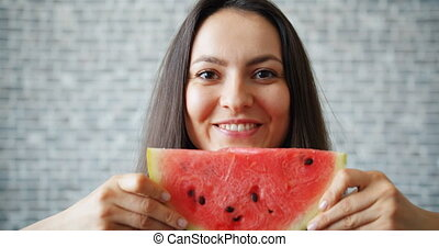 Portrait of girl holding water melon smiling hiding face on...